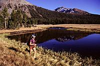A woman running by a pond in the yosemite national park high country