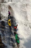 Two men rappelling down a waterfall while kayaking in the Sierras