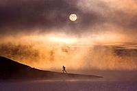 A man running along the shore of a misty lake at dawn near Truckee California