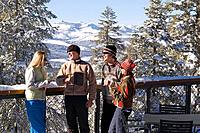 Four friends enjoying white wine on the deck of a ski lodge on a snowy day while talking and laughing at Northstar near Lake Tahoe