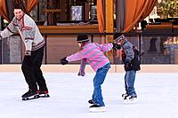 Two children chasing their father while skating at Northstar ski resort near Truckee California