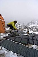 A woman cleaning snow off solar panels on the Biafo glacier in the Karakoram himalaya of Pakistan