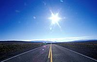 USAUtah road leading to horizon with sun burst in the sky