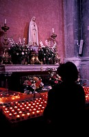 Baixa, Church of Sao Domingos, interior, woman lighting candle , Lisbon, Portugal, Europe