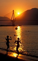 Rio-Antirio Bridge, sunset, women playing volley on beach , Patras, Achaia, Peloponnese, Greece 