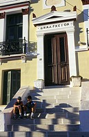 Children sitting on the stairs of the Town Hall in Hora, Serifos, Cyclades, Greece