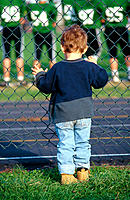 Young boy watching big kids football game