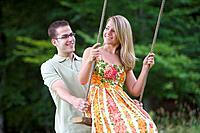 Man pushing girlfriend on swing