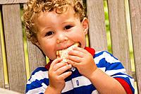 2-year-old boy eating a peanut butter sandwich