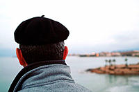 Man with beret looking at the sea