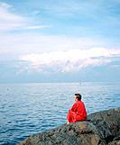 Boy looking at sea with bathrobe. Landsort Island. Sweden