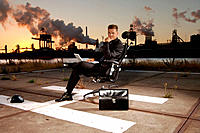 Businessman in swivelchair at sunset in industrial environment