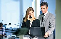 Businessman looking at computer, businesswoman talking on phone