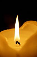 Close-up of burning candle. black background