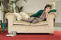 Sullen young woman on sofa (thumbnail)