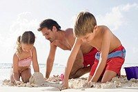A father making sandcastles with his children