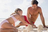 A father and daughter making sandcastles
