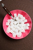 A bowl of sugar cubes and a spoon