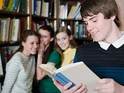 Girls looking at boy in library (thumbnail)