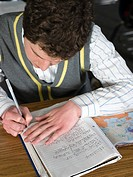 Boy writing in workbook