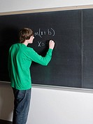 Boy writing on blackboard