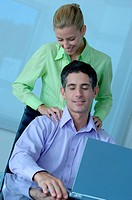 Businesswoman massaging businessman, smiling