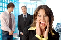 Businesswoman screaming with colleagues in background