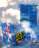 Blue chair in front of weathered blue wall with shutter (thumbnail)