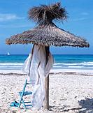 On the beach: parasol made of straw and a chair