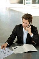 Businessman talking on a mobile phone at a desk