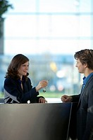 Receptionist giving the key of a hotel room to a businessman (thumbnail)