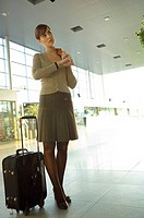 Businesswoman standing with her luggage at an airport lounge