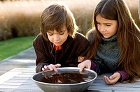 Close_up of two children looking into a bowl of water