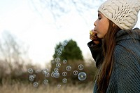 Side profile of a girl blowing bubbles with a bubble wand
