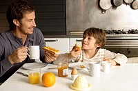 Mid adult man having breakfast with his son (thumbnail)