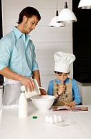Mid adult man making a cake with his son in the kitchen