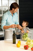 Mid adult man preparing food with his son in the kitchen