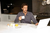 Mid adult man working on a laptop and having breakfast in the kitchen