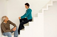 Mature man and a mid adult woman sitting on a staircase and looking at each other