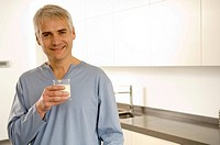 Portrait of a mature man holding a glass of milk (thumbnail)