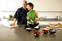 Mid adult woman preparing food with a mature man using a laptop in the kitchen