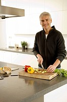 Portrait of a mature man chopping vegetables in the kitchen