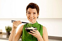 Portrait of a mid adult woman eating rice with chopsticks