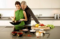 Mid adult woman preparing food with a mature man standing with arm around her in the kitchen