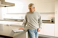 Mature man working on a laptop in the kitchen