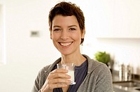 Portrait of a mid adult woman holding a glass of milk