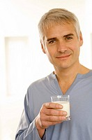 Portrait of a mature man holding a glass of milk