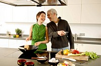 Mature man and a mid adult woman preparing food in the kitchen