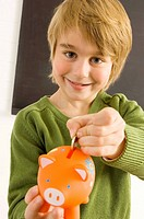 Boy putting a coin into a piggy bank