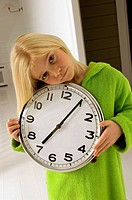 Portrait of a girl holding a clock